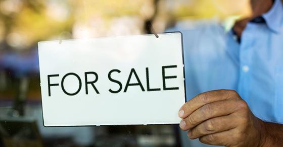 Man posting 'for sale' sign