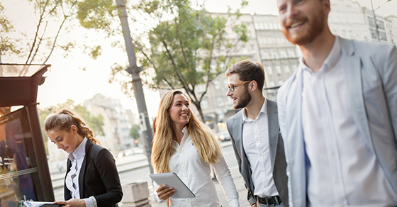 Business colleagues walking and talking on city streets