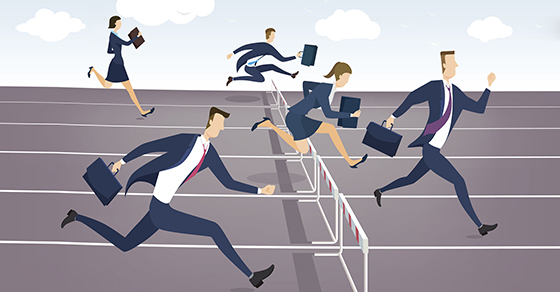 Businessman and businesswoman jumping over hurdles.