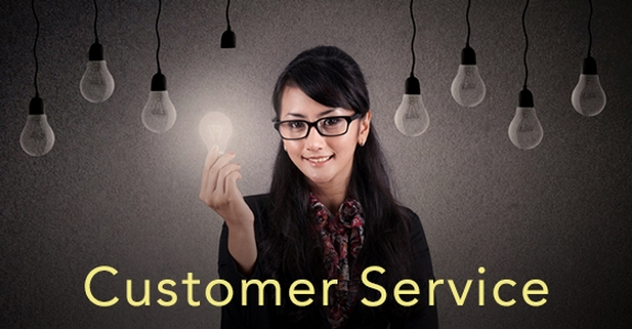 Businesswoman with glasses holds bright light bulb