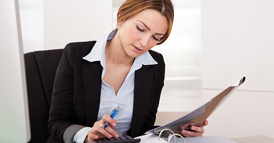 Businesswoman reading contents of binder