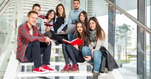 Medium group of students studying on steps of school building.