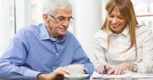 Man and woman looking at financial paperwork at table.